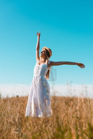 selective focus of sensual woman in white dress standing with outstretched hands and closed eyes on grassy field