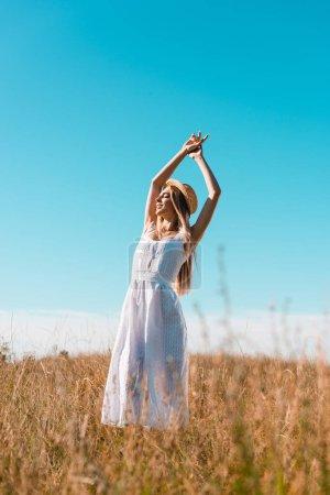 Photo pour Foyer sélectif de la femme élégante en robe blanche debout avec les mains levées et les yeux fermés dans les prairies contre le ciel bleu - image libre de droit