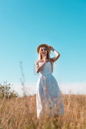 Photo pour Foyer sélectif de la femme blonde en robe blanche touchant chapeau de paille et tenant la main près du visage tout en se tenant dans le champ - image libre de droit