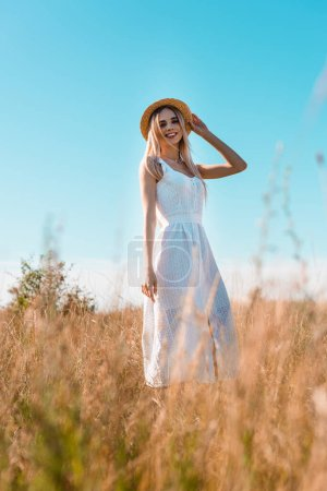 selective focus of young blonde woman in white dress touching straw hat while posing in field against blue sky