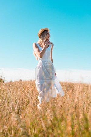 Photo pour Foyer sélectif de la femme élégante en robe blanche et chapeau de paille toucher le menton et regarder loin dans le champ contre le ciel bleu - image libre de droit