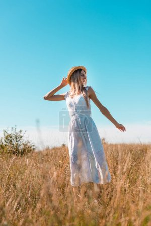 selective focus of blonde woman in white dress and straw hat showing follow me gesture in grassy meadow