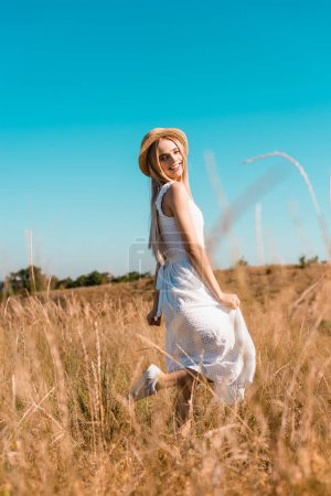 selective focus of woman in white dress and straw hat standing on one leg while posing in meadow