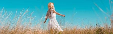 Photo pour Tête du site de la femme en robe blanche et chapeau de paille debout avec les mains tendues sur le terrain contre le ciel bleu - image libre de droit