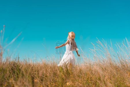 selective focus of woman in straw hat and white dress standing with outstretched hands on grassy field