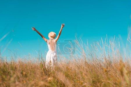 Photo pour Vue arrière de la femme en chapeau de paille et robe blanche debout avec les mains levées sur prairie herbeuse, mise au point sélective - image libre de droit