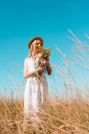 selective focus of blonde woman in straw hat and white dress holding bouquet of wildflowers against blue sky