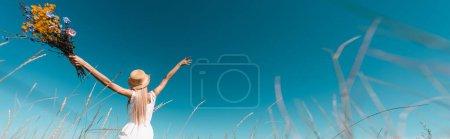 Photo pour Foyer sélectif de la femme en chapeau de paille et robe blanche tenant des fleurs sauvages tout en se tenant avec les mains levées, tir panoramique - image libre de droit