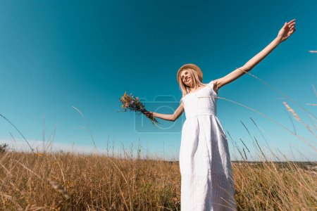 low angle view of stylish woman in white dress holding bouquet of wildflowers while standing with outstretched hands