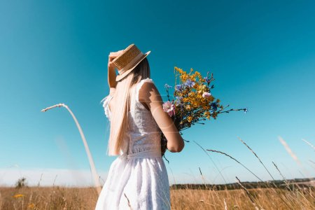 selective focus of young woman in white dress touching straw hat while holding bouquet of wildflowers against blue sky
