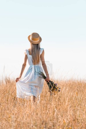 back view of woman in straw hat touching white dress while walking in grassy meadow with bouquet of wildflowers