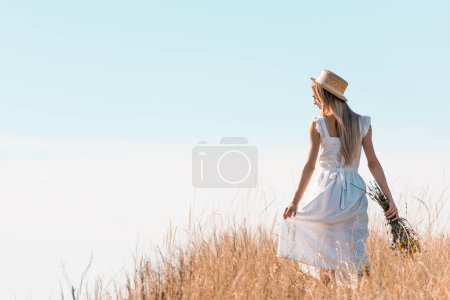 back view of young woman in straw hat touching white dress while holding wildflowers on grassy hill