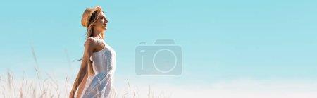 Photo pour Vue latérale de la jeune femme en robe blanche et chapeau de paille debout contre le ciel bleu avec les mains tendues, vue panoramique - image libre de droit