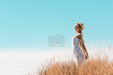 Photo for Side view of young woman in white dress and straw hat standing with closed eyes on grassy hill - Royalty Free Image