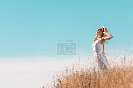 Photo pour Foyer sélectif de la jeune femme en robe blanche touchant chapeau de paille tout en se tenant debout sur la colline herbeuse contre le ciel bleu - image libre de droit