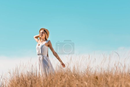 Photo for Selective focus of sensual woman in white dress touching straw hat while standing with outstretched hands against blue sky - Royalty Free Image