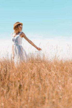Photo pour Foyer sélectif de femme blonde en robe blanche et chapeau de paille montrant me suivre geste dans prairie herbeuse - image libre de droit