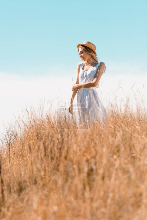 selective focus of young woman in white dress and straw hat looking away while standing on grassy hill