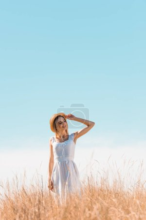 young woman in white dress standing on grassy hill, touching straw hat and looking away against blue sky