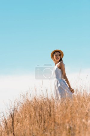 selective focus of young woman in straw hat touching white dress while standing on grassy hill