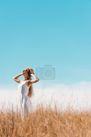 selective focus of stylish woman in white dress touching straw hat while standing with raised head against bule sky