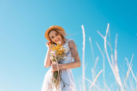 selective focus of woman in white dress touching hair while holding wildflowers and looking at camera, low angle view