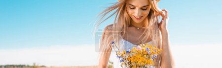 panoramic crop of sensual blonde woman holding bouquet of wildflowers against blue sky