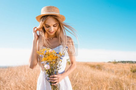 sensual young woman in white dress and straw hat holding wildflowers and touching hair in grassy meadow