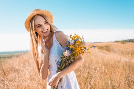 blonde, sensual woman in straw hat and white dress holding wildflowers and looking away in meadow