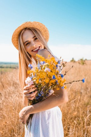 young stylish woman in straw hat holding wildflowers while looking at camera in grassy field