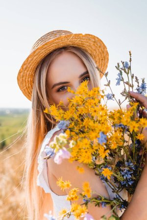 Photo for Sensual blonde woman in straw hat holding wildflowers and looking at camera against sky - Royalty Free Image