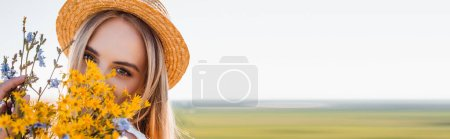 panoramic shot of blonde woman in straw hat holding wildflowers and looking at camera against clear sky and green field
