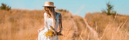 Photo pour Image horizontale de femme blonde en chapeau de paille touchant robe blanche tout en se tenant dans le champ avec bouquet de fleurs sauvages - image libre de droit