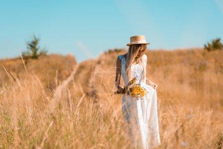 Photo pour Jeune femme blonde en chapeau de paille touchant robe blanche tout en se tenant dans le champ avec bouquet de fleurs sauvages - image libre de droit
