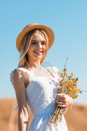 young woman in white dress and straw hat holding bouquet of wildflowers and looking at camera against blue sky