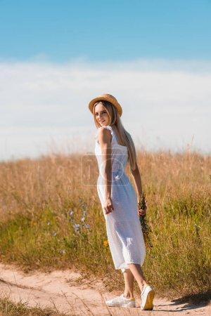 Photo pour Jeune femme blonde en chapeau de paille et robe blanche tenant des fleurs sauvages et regardant la caméra tout en marchant sur la route dans le champ - image libre de droit