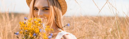young blonde woman in straw hat looking at camera while holding wildflowers, horizontal image