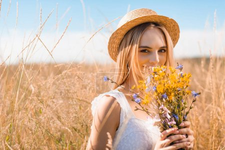 young blonde woman in straw hat looking at camera while holding wildflowers in grassy meadow
