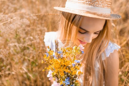high angle view of sensual blonde woman in straw hat holding bouquet of wildflowers in grassy meadow