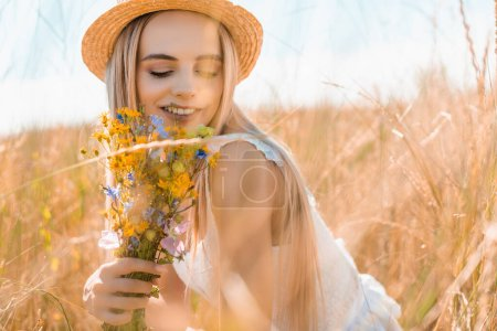 Photo for Selective focus of sensual woman in straw hat holding wildflowers in grassy field - Royalty Free Image