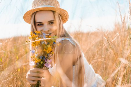 selective focus of young woman in straw hat holding wildflowers and looking at camera in grassy meadow