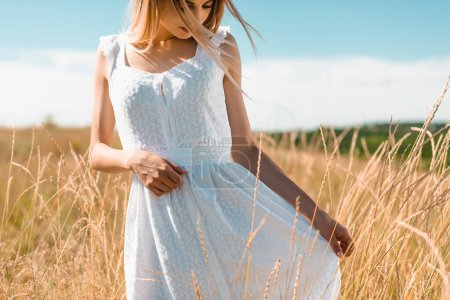 young woman touching white dress while standing in grassy field