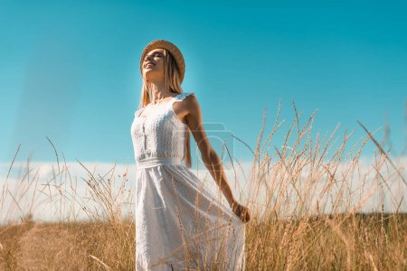 selective focus of young woman in straw hat touching white dress while standing with closed eyes in grassy meadow