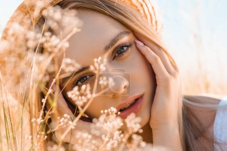 Photo for Portrait of pensive blonde woman in straw hat touching face while looking at camera near wildflowers - Royalty Free Image