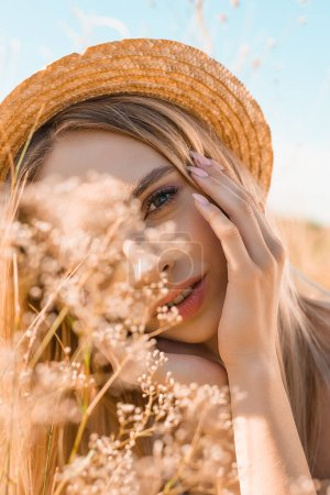 portrait of dreamy blonde woman in straw hat touching face and looking at camera near wildflowers