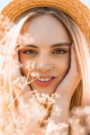 Photo for Portrait of sensual blonde woman in straw hat looking at camera and touching face near wildflowers - Royalty Free Image