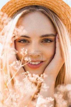 Photo pour Portrait de femme blonde sensuelle en chapeau de paille regardant la caméra et touchant visage près de fleurs sauvages - image libre de droit