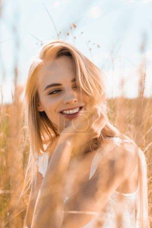 Photo pour Foyer sélectif de la jeune femme blonde tenant la main près du visage tout en regardant loin dans les prairies - image libre de droit