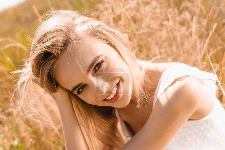 sensual mujer rubia tocando el pelo mientras mira a la cámara en el sol