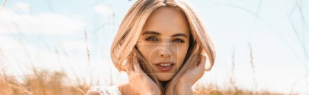 Photo for Panoramic concept of thoughtful blonde woman touching hair while looking at camera against blue sky - Royalty Free Image